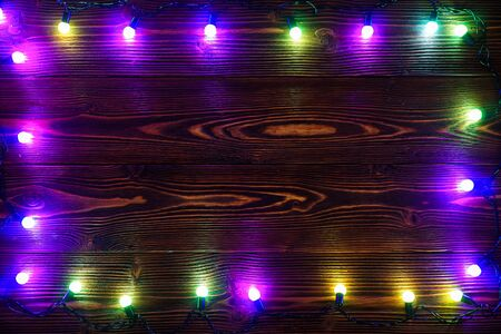 Wreath and garlands of colored light bulbs.Christmas background with lights and free text space. Christmas lights border. Glowing colorful Christmas lights on a wooden background. New Year.