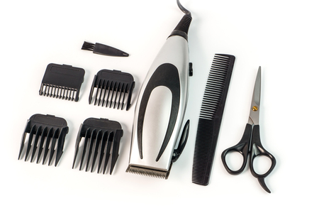 The machine for a hairstyle with attachments, comb and scissors. Barbershop. Hair clippers isolated on white background.