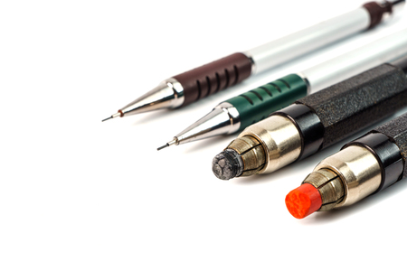 A few pencils with cores of different thicknesses and colors, on a white background.