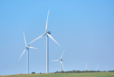 Wind turbines generating electricity on blue sky background - th