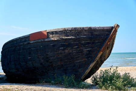 Old abandoned wooden fishing boat with rusted nails by the sea. Imagens