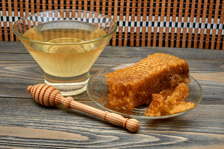 Honey with honeycombs on a glass plate isolated on a black background. 免版税图像