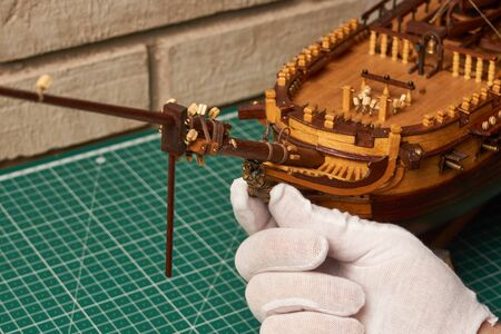 Installing the figurehead on the ship model. Assembly of ship model from wood. Standard-Bild