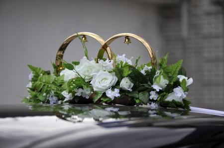 Les anneaux de mariage et bouquet de fleurs sur la voiture noire