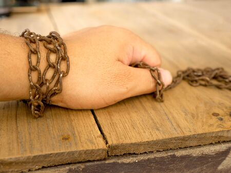enchain: The hand are tied with rusty chain for not to escape. Stock Photo