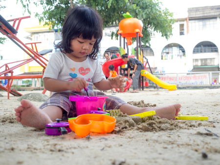 Little Asia girl sitting in the sandbox and playing whit toy shovel bucket and she was scooping in toy shovel bucket. Playing is a learning development and build muscle for children. Stock Photo