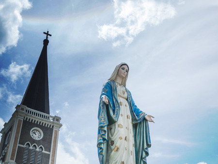The Blessed Virgin Mary Statue blue sky background. and behind the Virgin Mary, there are temples and crosses. On the sky there Sun halo Stock Photo