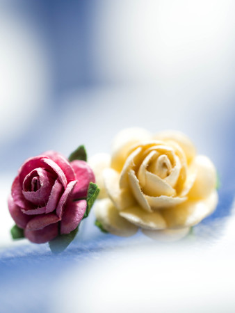 white fabric texture: Select focus at pink artificial flowers. pink and yellow artificial flowers made of paper and placed on blue cloth stripes. Green artificial leaves are around artificial flowers.