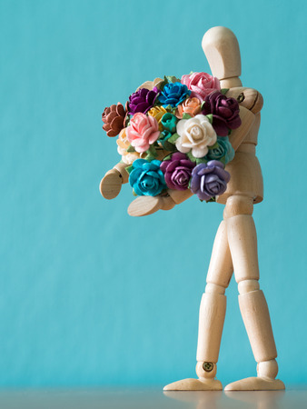 The wooden puppet holds flower and standing on the wood table. the background is blue and copy space for text Stock Photo