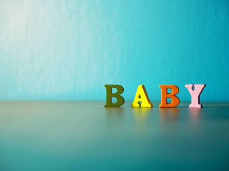 Baby. English alphabet made of wooden letter color. Alphabet baby on wooden table and background is powder blue.