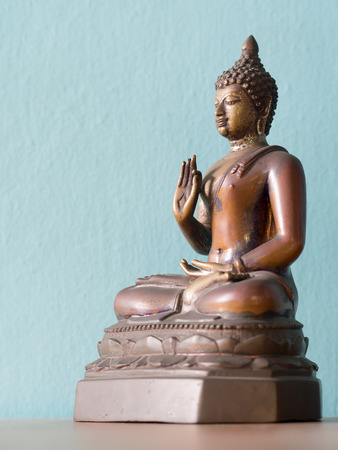 Antique Buddha Statue on wooden table. The background is Powder Blue (isolated) Stock Photo
