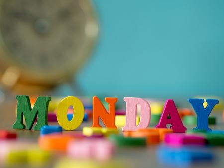 Цветное деревянное слово ПОНЕДЕЛЬНИК на деревянном столе и старинный будильник и фон - порошок синий. Английский алфавит из цветной буквы. Фото со стока