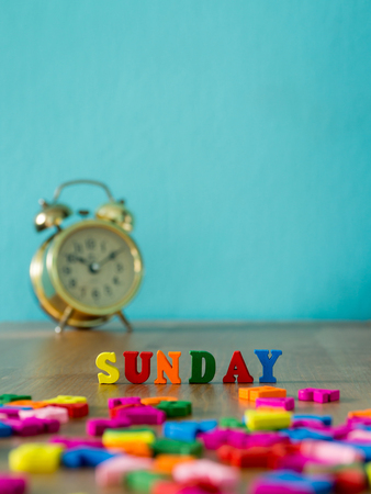 Colorful wooden word SUNDAY on wooden table and vintage alarm clock and background is powder blue. English alphabet made of wooden letter color.