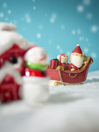Happy Santa Claus with gifts box on the snow sled going to house. near house have Snowman and Christmas Tree. Santa Claus and house on the snow. Christmas and happy new year concept.