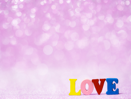 LOVE text on pink abstract glitter background with bokeh. lights blurry soft pink for the romance background and background copy space for text. Valentines day, love concept and love background Stock Photo