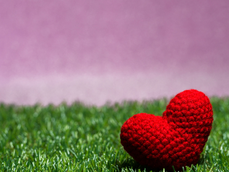 Handmade red yarn heart on Green grass background is royal pink.Copy space for text, Valentines day, love concept and love background