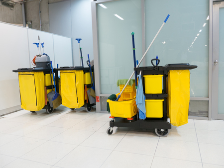 Cleaning Cart in the station. Cleaning tools cart and Yellow mop bucket wait for cleaning.Bucket and set of cleaning equipment in the airport office. Banque d'images