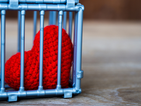 Heart in the cage Put on a wooden table, It shows the closure of freedom and love. Love is disappointed and not satisfied. Closing and blocking in love Stock Photo