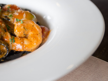 Black Spaghetti in tomato sauce with shrimp, tomato sprinkle with spices and cheese on white plate.Fresh and clean dishes look delicious and yummy
