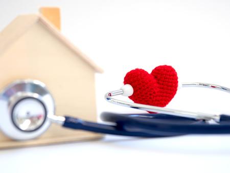 rotes Herz unter Verwendung des Stethoskops auf dem blauen Hintergrund für Hausgesundheitscheck. Konzept der Liebe und des interessierenden geduldigen Hauses auswendig. Kopieren Sie Platz für den Text und den Inhalt