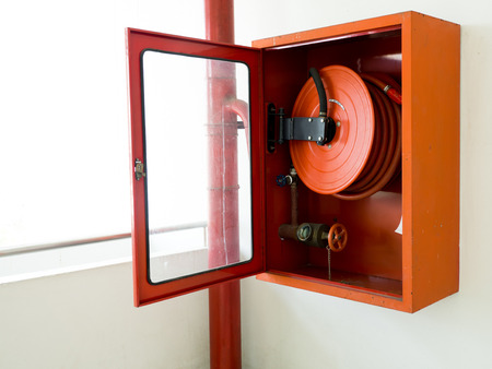 Fire extinguisher with various types of fire extinguishers Located In the white wall. copy space for text and content Banco de Imagens