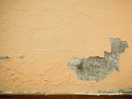 Old Paint peeling plaster walls damage surface. A background of peeling paint, the old paint texture is chipping and cracked fall destruction.