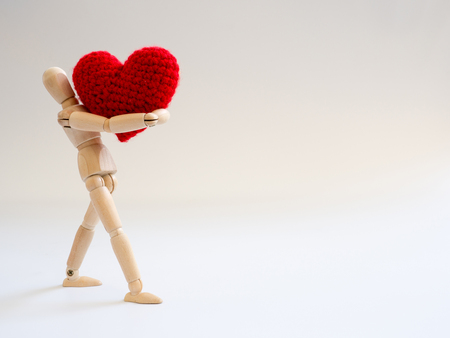 Wooden puppet standing and holding a red heart on the white screen background. Wooden puppet holding the heart with love and care. Archivio Fotografico