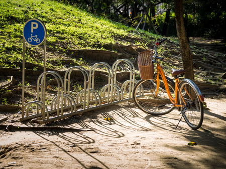 Yellow bike parked at bicycle parking in the park. The side is a bicycle parking sign. There is golden light on the floor. energy conservation concept Stok Fotoğraf