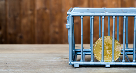 The coin is in the gray nick color put on a wooden table. The concept of investment and fluctuation of bitcoin and cryptocurrency. Stok Fotoğraf