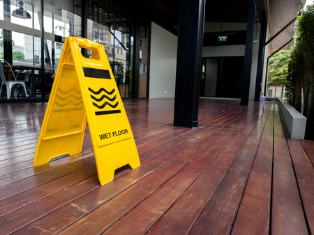 yellow plastic cone with sign showing warning of wet floor in restaurant