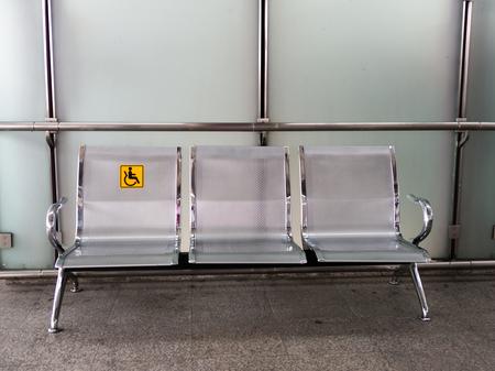Krzesła ze stali nierdzewnej na dworcu z oznakowaniem dla osób niepełnosprawnych ułatwiające korzystanie z pociągów osobom niepełnosprawnym.