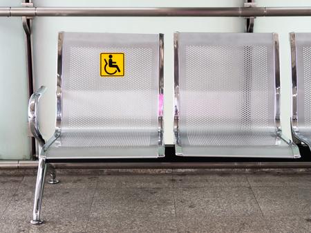 Krzesła ze stali nierdzewnej na dworcu z oznakowaniem dla osób niepełnosprawnych ułatwiające korzystanie z pociągów osobom niepełnosprawnym. Zdjęcie Seryjne