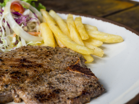 close up of T-bone steak with salt and pepper, golden french fries and green vegetables. on white plate, Fork and knife, wooden table in the restaurant Standard-Bild - 110368153