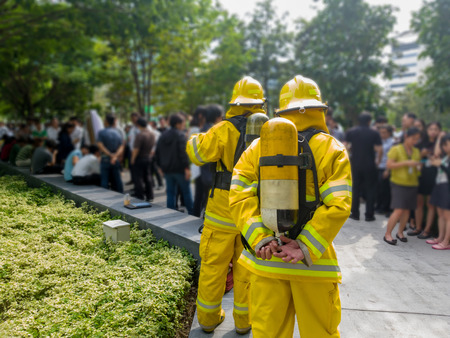 Select focus of back Firefighters in yellow suit with an oxygen tank in the back. Firefighters are teaching office workers to escape from high-rise buildings (Fire Drill). Standard-Bild - 110368157