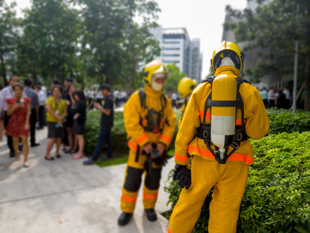 Select focus of back Firefighters in yellow suit with an oxygen tank in the back. Firefighters are teaching office workers to escape from high-rise buildings (Fire Drill). Standard-Bild - 110368193