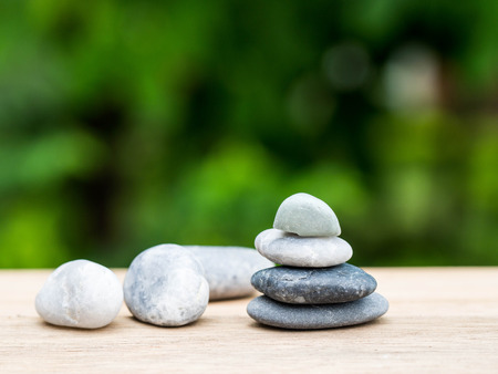 Four stones stacked placed on a wooden board. The backdrop is black on green. Standard-Bild - 110368196