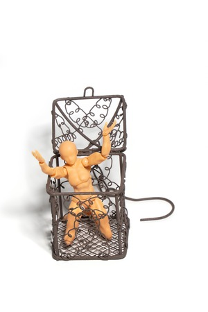 Action figure sitting and hold two hands above the head in open steel cage on isolate background, Concept of tolerance in comfort zone do not dare to change and Fear of change Standard-Bild - 110368202