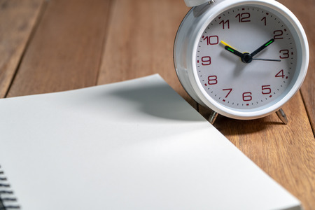 Empty notebook with white vintage alarm clock on the wooden table. Copy space for add text. Standard-Bild - 110368208