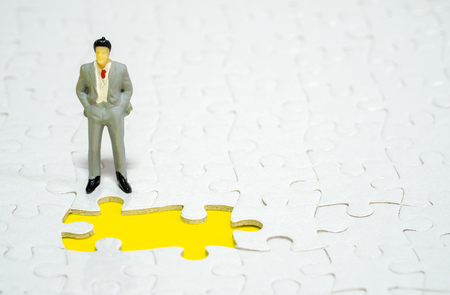 businessman standing in front of  missing piece jigsaw on the yellow background. Standard-Bild - 110368233