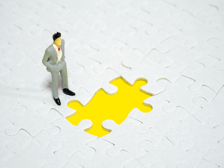 businessman standing in front of  missing piece jigsaw on the yellow background. Standard-Bild - 110368235