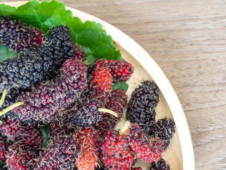 Close up of mulberry with a green leaves on the wooden plate on wooden table. Mulberry this a fruit and can be eaten in have a red and purple color and delicious and sweet nature. Standard-Bild - 110368246