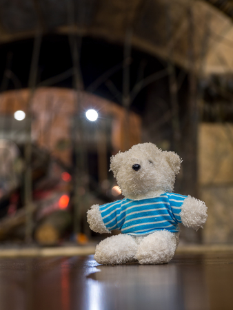 White teddy bear wearing blue shirt sitting on the wood table in front of the fireplace copy space for text. Standard-Bild - 110368269