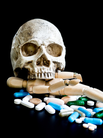 Human skull on multicolored of drug and capsule is on the black background. Close up. We are against drugs (anti drugs), cure in container for health.Heap of green blue white round capsule pills Standard-Bild - 110368302