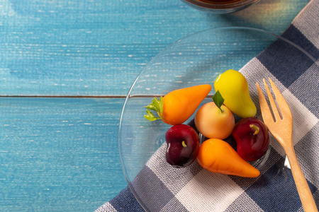 colorful of deletable imitation fruits (KANOM LOOK CHOUP is Thai snack) put on a glass plate with a wooden spoon on a blue tablecloth on blue wooden table Standard-Bild - 110721281