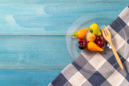 colorful of deletable imitation fruits (KANOM LOOK CHOUP is Thai snack) put on a glass plate with a wooden spoon on a blue tablecloth on blue wooden table Standard-Bild - 110721283