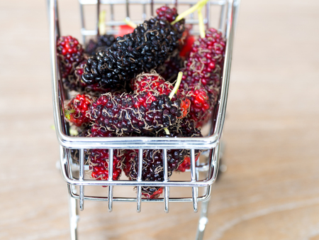 Close up group of mulberries in red shopping cart on wooden table. Mulberry this a fruit and can be eaten in have a red and purple color. Mulberry is delicious and sweet nature. Standard-Bild - 110721284