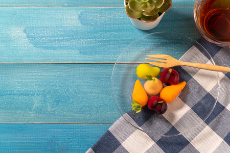 colorful of deletable imitation fruits (KANOM LOOK CHOUP is Thai snack) put on a glass plate with a wooden spoon and Tea cup on a blue tablecloth on blue wooden table Standard-Bild - 110721287