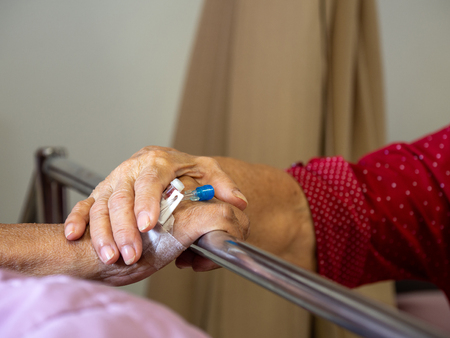 Wife visiting husband in hospital. Senior couple holding hands on hospital bed for hospitalization for supporting his dear. Concept of love and to be with lover. Standard-Bild - 110721291