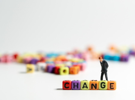 miniature figure businessman in dark blue suit standing backside of colorful of CHANGE alphabet and thinking of the change will come. Archivio Fotografico