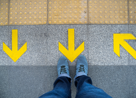 Top view of man feet standing over Arrow symbol on subway platform. Yellow arrow sign on floor at the train station. Reklamní fotografie